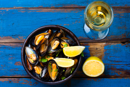 almejas: Mussels in clay bowl, glass of white wine and lemon on wooden blue background Stock Photo