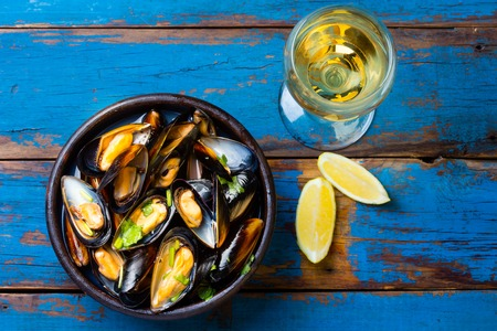 sopa: Mussels in clay bowl, glass of white wine and lemon on wooden blue background Stock Photo