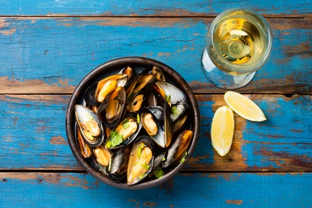 Mussels in clay bowl, glass of white wine and lemon on wooden blue background Standard-Bild