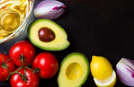 Ingredientes para la salsa de guacamole latino americana en el fondo de piedra negro