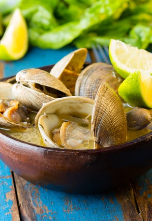 almejas: Seafood soup of clams in clay bowl on wooden blue background.  Mariscal or paila marina Stock Photo