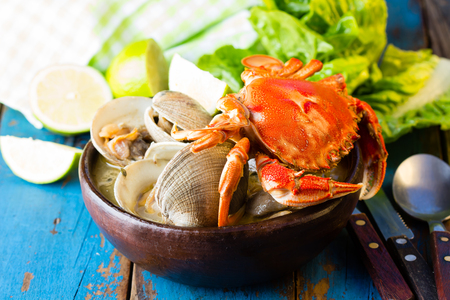 almejas: Seafood soup of clams and crab in clay bowl on wooden blue background.  Mariscal or paila marina Stock Photo