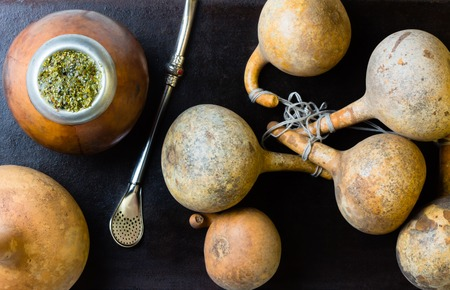 latina america: Yerba Herb mate in calabash and calabashes on black background. Top view