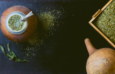 latina america: Yerba mate in calabash and dry herb in clay bowl on black background. Top view