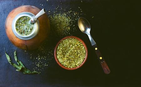 yerba mate: yerba mate en hierba de calabaza y seca en un recipiente de arcilla en el fondo negro. Vista superior