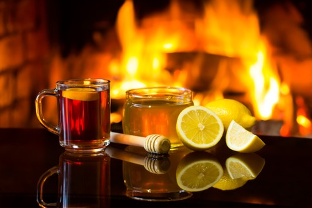 Cup of hot drink wine, bowl of honey and lemon in front of warm fireplace. Magical relaxed cozy atmosphere near fire.