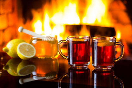atmosphere: Two cups of hot drink wine tea, bowl of honey and lemon in front of warm fireplace. Magical relaxed cozy atmosphere near fire.