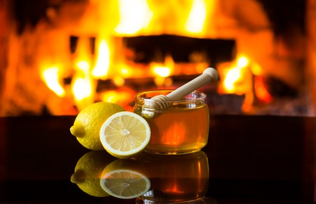 Bowl jar of honey and lemon in front of warm fireplace. Magical relaxed cozy atmosphere near fire.
