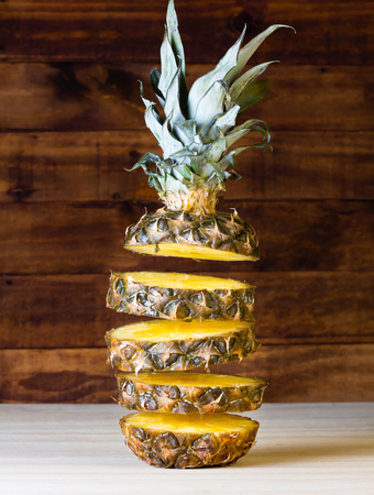 Flying slices of pineapple on wooden background.