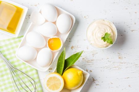 Verse zelfgemaakte witte saus Mayonaise en ingrediënten eieren, citroen olijfolie op witte achtergrond. Bovenaanzicht Stockfoto