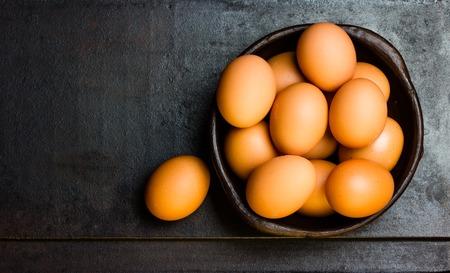 Eggs in clay dark bowl on black background