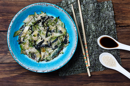 white sesame seeds: Asian food. Asian salad with seaweed nori, cucumber, white sesame seeds and soya in blue bowl on wooden rustic background. Top view