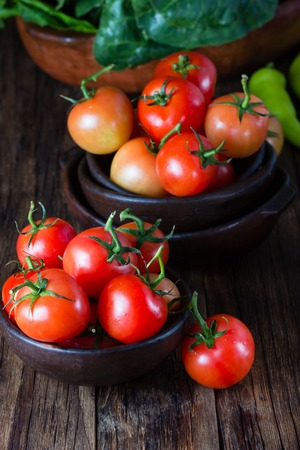 Ripe natural tomatoes with leaves in clay bowl on wooden rustic background. Closeup