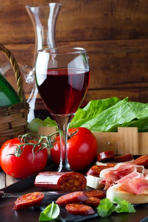 accompanied: Ham Serrano and salami with bread accompanied by glass of red wine Stock Photo