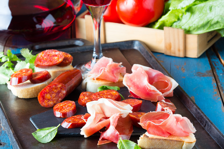 Ham Serrano and salami with bread accompanied by glass of red wine Stock Photo