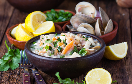 almejas: Latin American food. Seafood shellfish ceviche raw cold soup salad of seafood shellfish almejas, lemon, cilantro onion in clay bowl on wooden background. Traditional dish of Peru or Chile Stock Photo