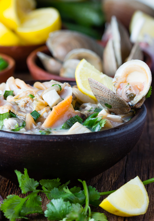 Latin American food. Seafood shellfish ceviche raw cold soup salad of seafood shellfish almejas, lemon, cilantro onion in clay bowl on wooden background. Traditional dish of Peru or Chile Standard-Bild