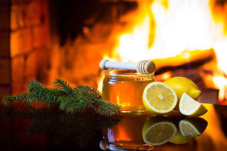 Christmas New Year composition. Jar of bee honey, lemon with christmas decoration - fir branches in front of warm fireplace. Relaxed, magical, cozy atmosphere near fireplace Stock Photo