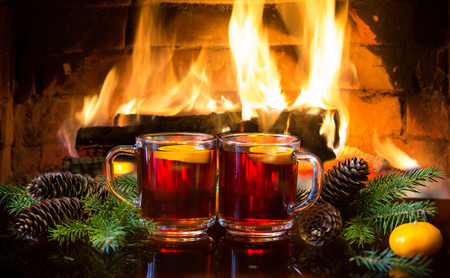 atmosphere: Christmas New Year composition. Two glasses of mulled red wine or hot drink tea with christmas decoration - fir branches in front of warm fireplace. Romantic, relaxed magical atmosphere near fireplace