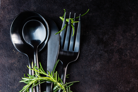 tea spoon: Set of black cutlery knife, spoon, tea spoon, fork with rosemary on black stone background. Top view Stock Photo