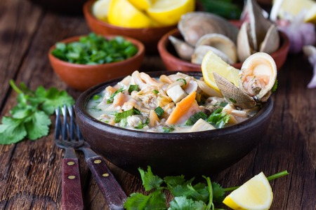 Latin American food. Seafood shellfish ceviche raw cold soup salad of seafood shellfish almejas, lemon, cilantro onion in clay bowl on wooden background. Traditional dish of Peru or Chile Stock Photo