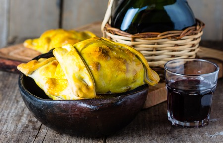 Empanadas. Latin American chilean food. Typical traditional Chilean empanadas with meat, onion, eggs and olives on mapuche rustic cutting board, two glasses and bottle of red wine
