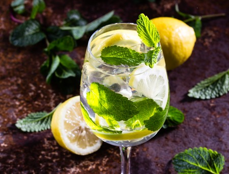 Glass of alcohol cocktail or lemonade. Mohito cocktail with lemon, mint, ise cubes. Cold drink. Fresh lemons and mint on wooden background