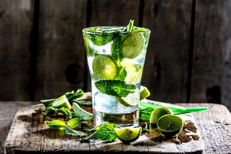 mohito: Glass of alcohol cocktail or lemonade. Mohito cocktail with lemon, lime, mint, ise cubes. Cold drink. Fresh lime and mint on wooden background