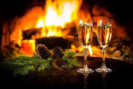 スパーク リング白ワインと暖かい暖炉の前で正月クリスマス装飾の 2 つのグラス。ロマンチックな居心地の良いリラックスした幻想的な雰囲気火の