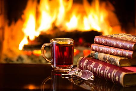 温かい飲み物やアルコール飲料または赤いホットワインと暖かい暖炉の前でアンティークの本のガラスのマグ。火のそばの魔法のリラックスした居 写真素材