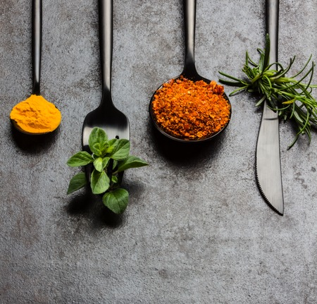 dryed: Food background with fresh herbs - rosemary and oregano, dryed spices - chili pepper, turmeric curcuma and black steel cutlery - knife spoon fork, tea spoon on black background. Top view. Copy space