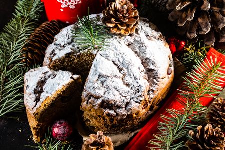 Christmas composition. Christmas cake - pan de pasqua - and Christmas New Year decoration - fir brunches, fir and pine cones, New Year balls, red napkin on black background Stock Photo