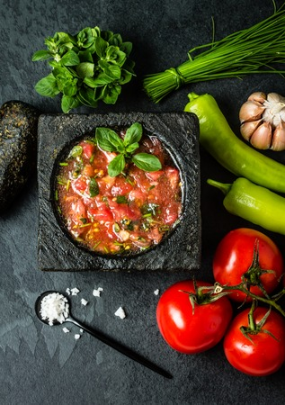 chilean: Traditional Latin American mexican Tomato sauce salsa, chilean chancho en piedra in stone mortar and ingredients tomatoes, chile, garlic, onion, sea salt on dark slate stone background. Top view Stock Photo