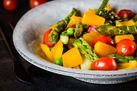 Mediterranean vegetarian salad. Vegan salad with asparagus, cherry tomatoes, yellow bell pepper on gray plate on black slate stone background. Vegetarian or healthy food. Top view Stock Photo