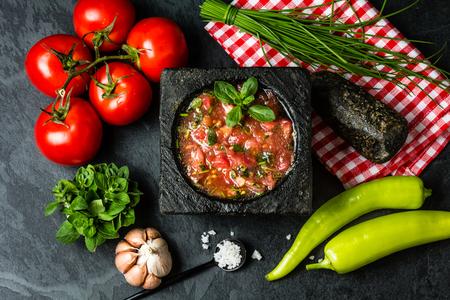 伝統的なラテン アメリカ メキシコ トマト ソースのサルサ、チリ chancho en ピエドラ石モルタルや食材トマト、チリ、ニンニク、タマネギ、暗いスレ