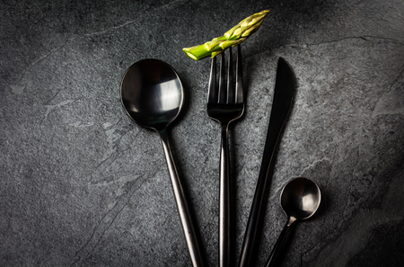 tea spoon: Set of black cutlery knife, spoon, tea spoon, fork with asparagus on black stone slate background. Top view. Copy space Stock Photo