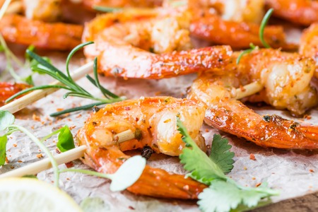 king size: Seafood. Shelfish. Grilled fried Shrimps Prawns on wooden skewers with spices and fresh herbs on wooden rustic cutting table on wooden background. Srimps prawns brochette kebab. Barbecue srimp