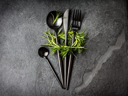 tea spoon: Set of black cutlery knife, spoon, tea spoon, fork with rosemary on black stone slate background. Top view. Copy space Stock Photo