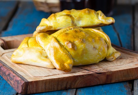 Empanadas. Latin American chilean food. Typical traditional Chilean empanadas with meat, onion, eggs and olives on mapuche rustic cutting board on wooden blue background Stock Photo