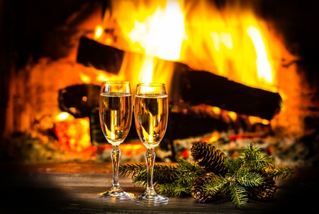 atmosphere: Two glasses of sparkling white wine and New Year Christmas decoration in front of warm fireplace. Romantic, cozy relaxed magical atmosphere near fire. New Year or Christmas concept