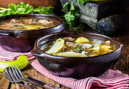 sopa: Chilean meat soup ajiaco. Latinamerican food. Ajiaco - traditional chilean soup with grilled meat, onion and potato served in clay plate from pomaire Chile