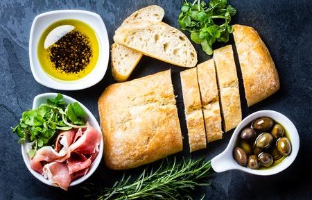 Bread ciabatta, jamon ham serrano paleta iberica, arugula, olive pepper oil, olives, rurosemary and glass of red wine on stone slate black background. Top view copy space