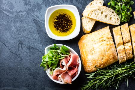 Bread ciabatta, jamon ham serrano paleta iberica, arugula, olive pepper oil, rosemary and glass of red wine on stone slate black background. Top view copy space