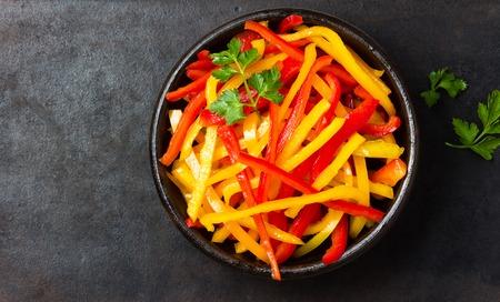 Insalata rossa e gialla della paprica del peperone dolce in ciotola dell'argilla su fondo nero. Vista dall'alto. Copia spazio