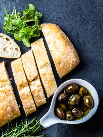Bread ciabatta, arugula, olives, rosemary on stone slate black background. Top view