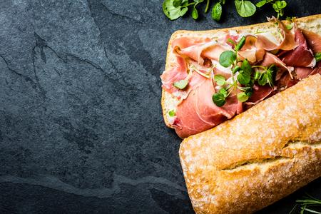 Ciabatta sandwich with jamon ham serrano paleta iberica, arugula, rosemary on stone slate black background. Top view Foto de archivo