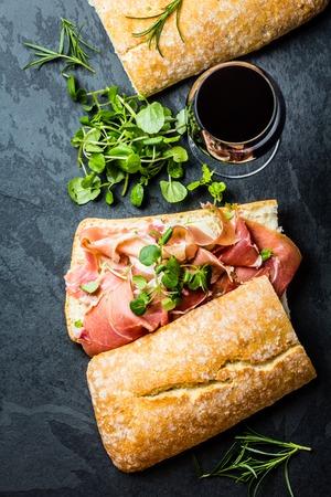 Ciabatta sandwich with jamon ham serrano paleta iberica, arugula, rosemary and glass of red wine on stone slate black background. Top view