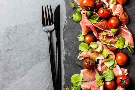 Salad with ham jamon serrano, cherry tomatoes, arugula on black stone slate board, grey background. Top view Stock Photo