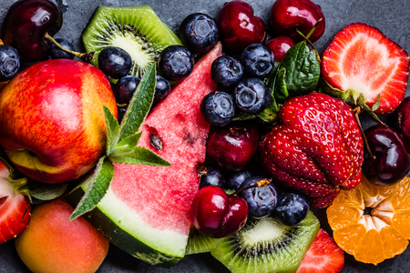 Assortment of summer fresh berries and fruits. Mix of blueberry, cherry, kiwi watermelon, strawberry, tangerine, mandarin peach, clementine on black slate plate on black slate plate. Top view