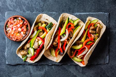 メキシコ産豚肉と野菜のサルサのタコス。黒い石のタコス アル牧師スレート板黒の背景に。トップ ビュー